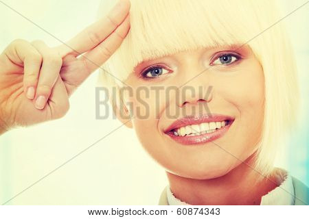 Attractive business woman saluting.