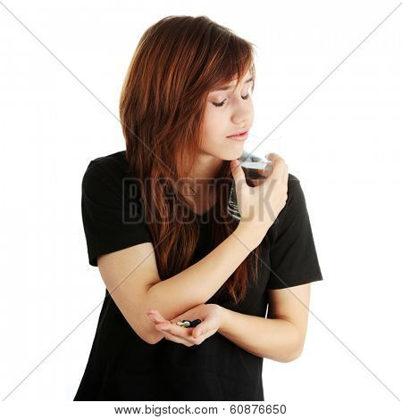 Young caucasian woman with glass of water taking pills,isolated on white background