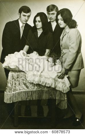 LODZ, POLAND,CIRCA SEVENTIES- vintage photo of parents and godparents with a baby in traditional baby's sleeping bag for christening
