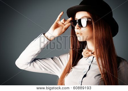 Elegant girl model poses in blouse, bow tie and bowler hat. Refined style of old Europe.