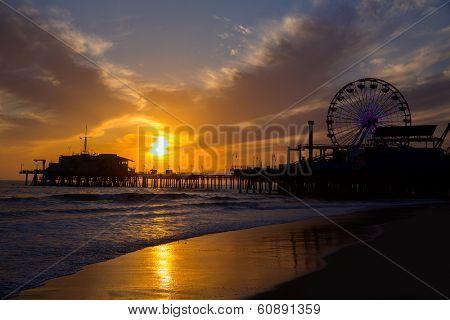 Santa Monica California sunset on Pier Ferris wheel and reflection on beach wet sand