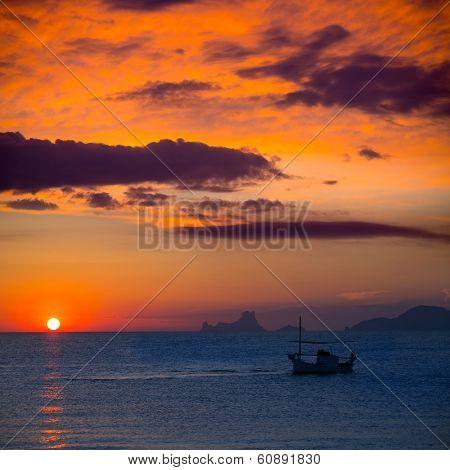 Ibiza sunset Es Vedra view and menorquina fisherboat from Formentera orange sky