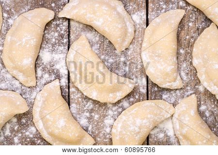 Uncooked pierogi on wooden table