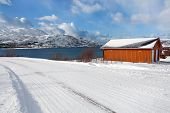 Isolated House Next To A Snowy Fjord
