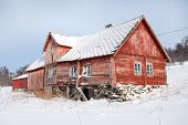 stock photo of tromso  - Abandoned red wooden house in Troms countryside during a snowy winter