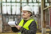 pic of substation  - Electrical Engineer with folder in the electric substation - JPG