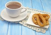 image of churros  - Cup of hot chocolate and several Churros