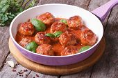 stock photo of meatball  - hot meatballs with tomato sauce in a frying pan on a wooden table - JPG