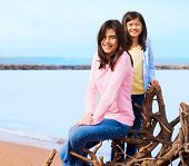 Two Sisters Sitting On Fallen Tree By Lake Shore In Summer