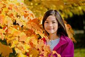 foto of biracial  - Little biracial asian girl standing amongst bright autumn leaves - JPG