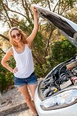 pic of frown  - Attractive young blond woman inspecting her car engine after a breakdown at the roadside frowning in annoyance and frustration - JPG