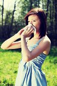 Young woman in summer dress standing on meadow during sunny day  and wiping her nose. Girl with runn