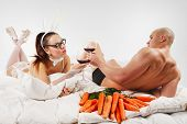 Lovely couple in rabbit costume lying  in bed with  glass of red wine and carrots