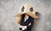 Businesswoman wearing carton box with drawings on head