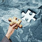 Concept of global help or working together, a hand holding a piece of puzzle of a world map.