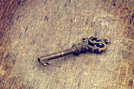pic of skeleton key  - Old ornate skeleton key on rough wood background with retro filter effect - JPG