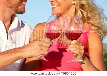 Toasting wine drinks - couple drinking glasses red wine or rose. Closeup of hands and mouth in toast