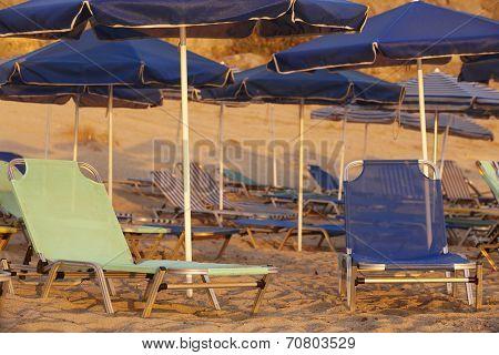 Sunbeds And Sunshades In A Mediterranean Beach. Crete