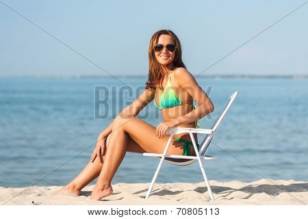 summer vacation, holidays and people concept - smiling young woman sunbathing in lounge on beach