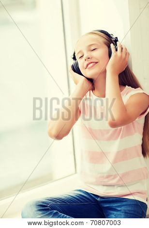 home, leisure, new technology and music concept - little girl with headphones at home