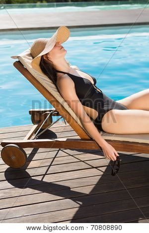 Side view of beautiful young woman in bikini relaxing by swimming pool