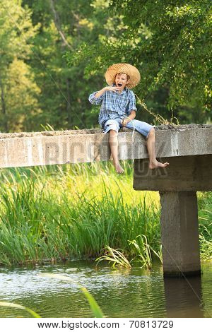 Boy fishing with rod at straw hat