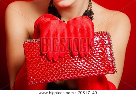 Female hands in red gloves holding a red clutch