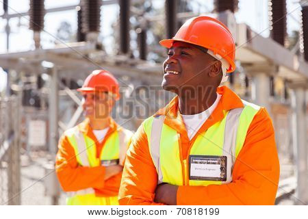 smiling african electrical engineer in substation with colleague on background