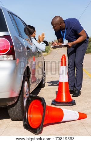 female african learner driver apologizing to instructor after running over traffic cone