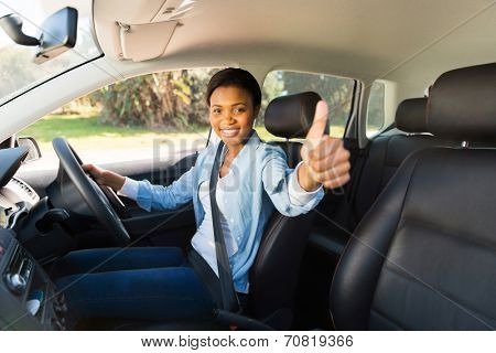 attractive young african female driver giving thumb up inside her new car