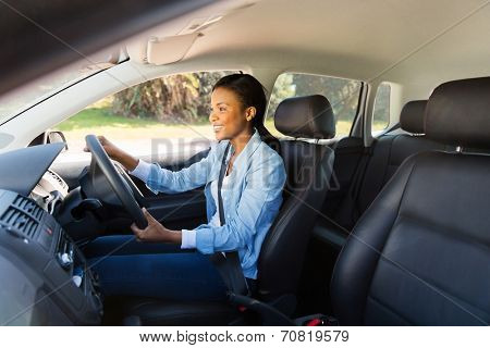 happy african woman driving a new car