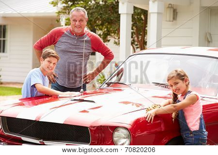 Grandfather With Grandchildren Cleaning Restored Classic Car