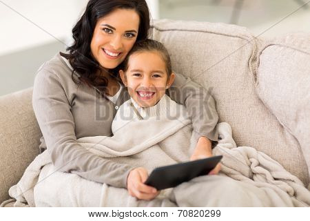 happy woman and her little daughter snuggle on couch wrapped with blanket