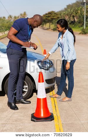 male african instructor marks checklist during a driving test
