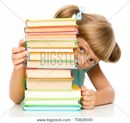 Cute little girl plays with pile of books while sitting at table, isolated over white