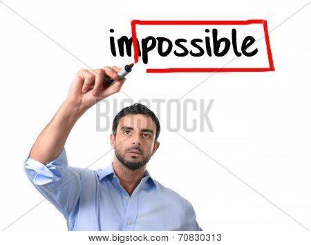 Businessman Turning Impossible Word Into Possible Writing With Red Marker