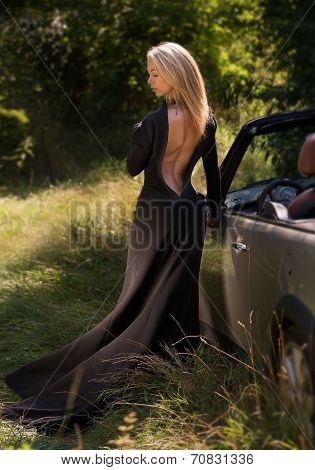 Sexy, elegant blonde woman in black long dress, outdoor, with cabrio car