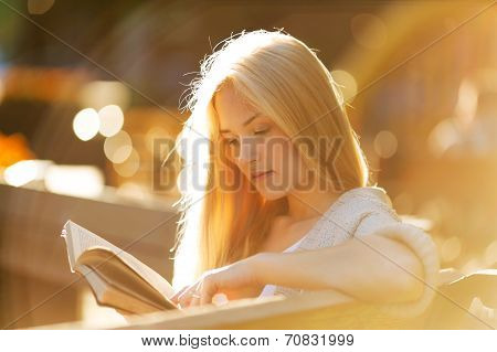 Happy Blonde Girl Reading A Book
