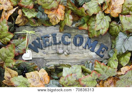 Distressed wood welcome sign with hearts and fall foliage border