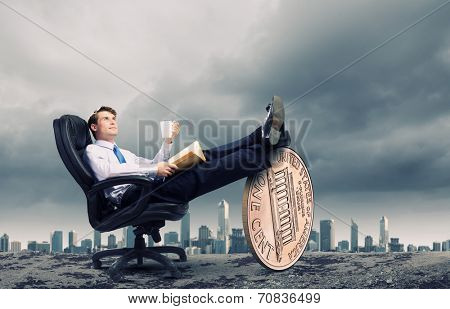 Young confident businessman sitting in chair with legs on cent coin