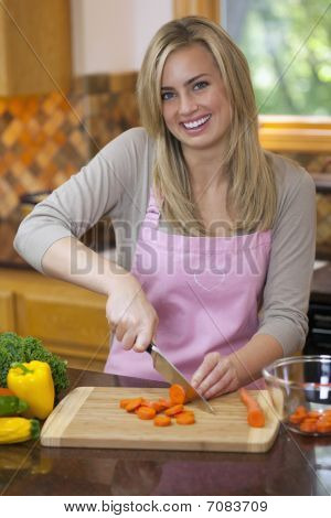 Woman Slicing Produce In Kitchen
