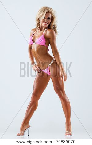 Smiling athletic woman in pink bikini showing muscles on gray background
