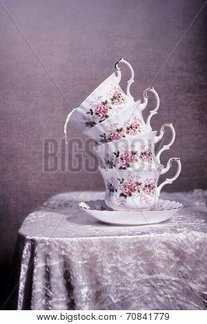 Stack of antique cups with splashed milk - vintage tone filter effect added