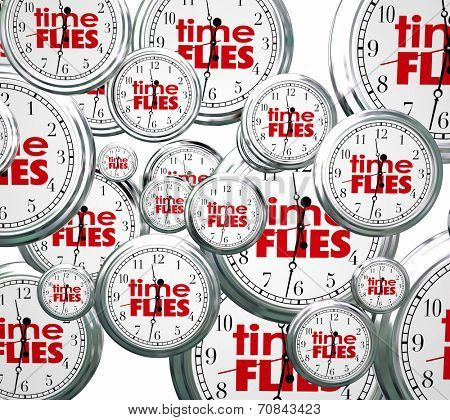 Time Flies words on 3d clocks flying by to symbolize the speed of hours, days, weeks, months and years passing too quickly