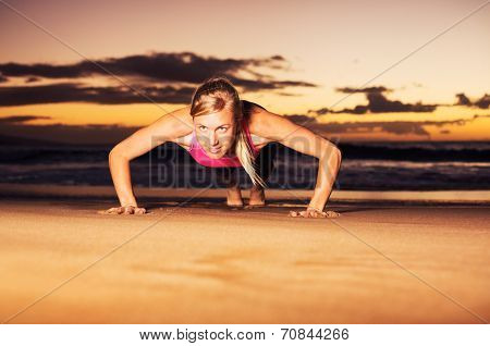 Fitness young woman doing push ups on beach at sunset. Outdoor workout.