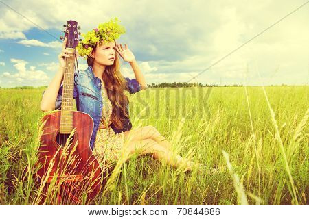 Romantic girl in a wreath of wild flowers playing her guitar. Summer. Hippie style.
