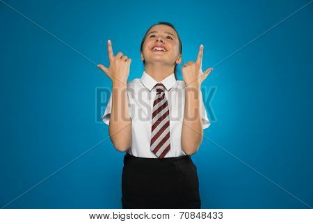 Happy young girl in school uniform standing with her head tilted back pointing above herself with both hands towards blank copyspace