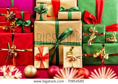 Three Piles Of Xmas Gifts In Red, Gold And Green