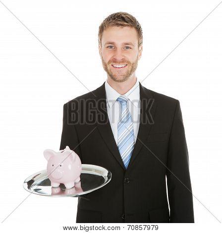 Businessman With Piggybank On Tray