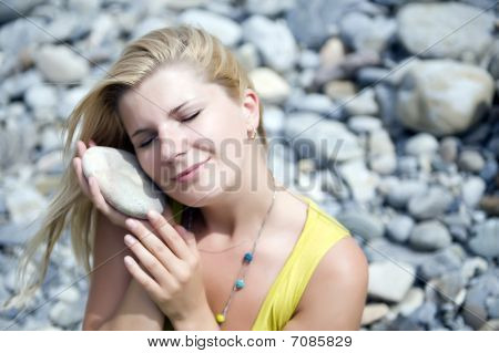 Young Beautiful Woman In Stone Zen Garden Holding Some Stones In Her Hands